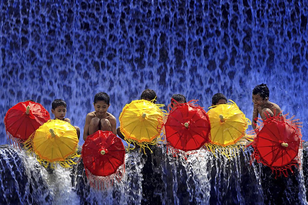 Vaikai žaidžia lietuje su skėčiais